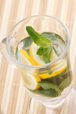 glass fresh water with mint and lemon on a bamboo table Stock Photo - 19324443