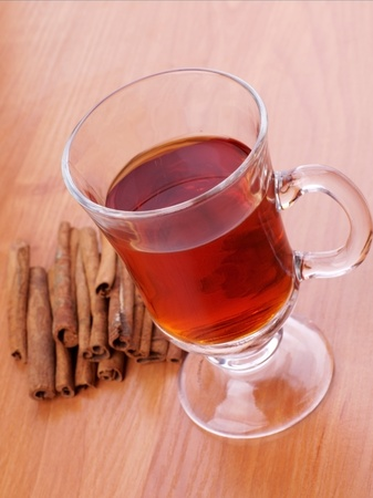 cup of hot black tea, cinnamon sticks on wooden table photo