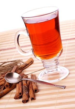 cup of hot black tea, cinnamon sticks on wooden table photo