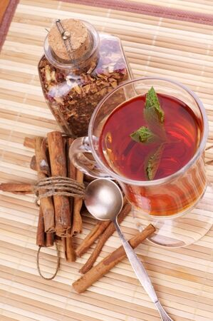 cup of hot black tea with mint, cinnamon sticks on wooden table photo