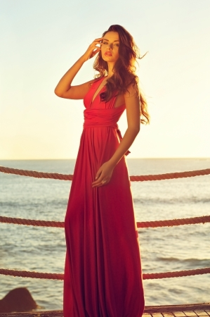 young beautiful elegant woman in pink dress standing near sea photo