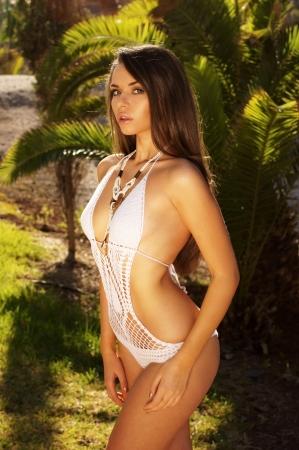 salud sexual: retrato de dama sexy en bikini blanco contra palmeras