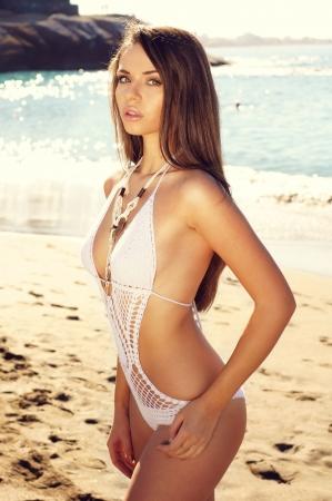hermosa joven sexy en traje de ba?lanco que presenta en la playa y mirando a puerta cerrada Foto de archivo