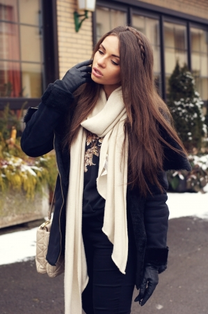 winter fashion: portrait of stylish young girl in black clothes