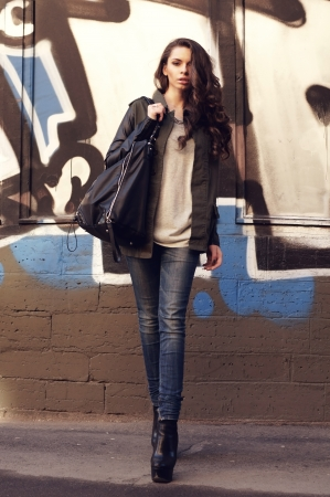 tall slim bautiful girl in stylish jacket, jamper, jeans and shoes standing against urban city wall