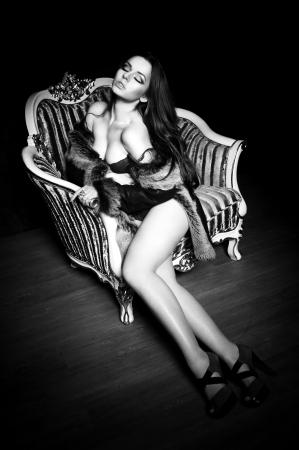 Студия Портрет молодой красивой чувственной женщины, сидя в старом кресле или ретро Фото со стока