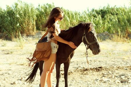 beautiful young woman with brown horse outdoors photo