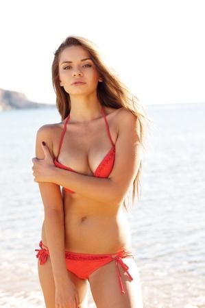 joven y bella mujer posando en bikini rojo en la playa