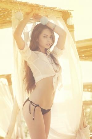 hermosa chica linda posando en cortinas en la playa de verano