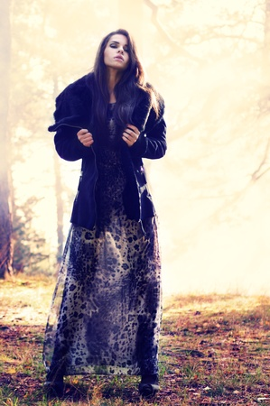 fur tree: fine art photo. young beautiful woman in mysterious smoke forest Stock Photo