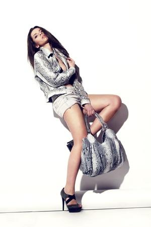 joven y bella modelo de moda femenina posando en reptiles chaleco de cuero con el bolso de cuero