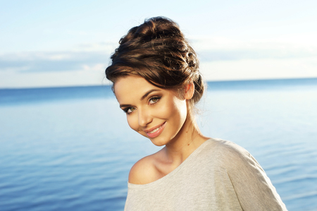 Pretty smiling young woman portrait against blue sea and sky. Stylish girl with hairdress. photo