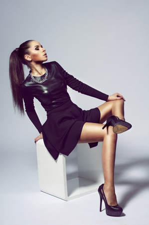 high heel shoe: Stylish girl posing (sitting) on white modern cube. Young woman wearing black dress and high heels. studio fashion model portrait.