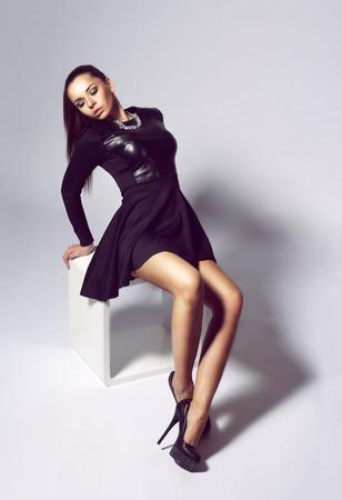 sexy girl sitting: moda vestito sexy ragazza seduta sul cubo bianco. giovane donna sexy in abito nero e tacchi neri. moda elegante modello girato in studio