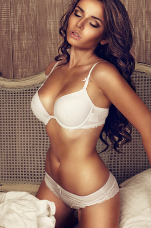 young beautiful sexy woman in white underwear standing in bed photo