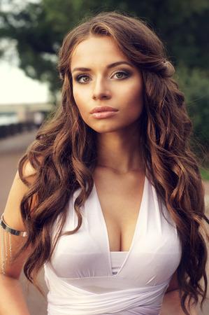al aire libre retrato de mujer joven y bonita con el peinado de rizos y en vestido púrpura