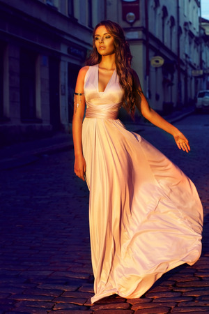 fashion portrait of young beautiful girl in pale lilac color long flying dress walking down the street in old town at sunset       Stok Fotoğraf