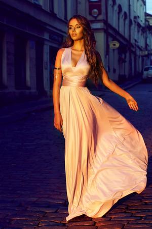 Retrato de moda de la hermosa joven en el color lila pálido vestido largo del vuelo caminando por la calle en el casco antiguo al atardecer Foto de archivo