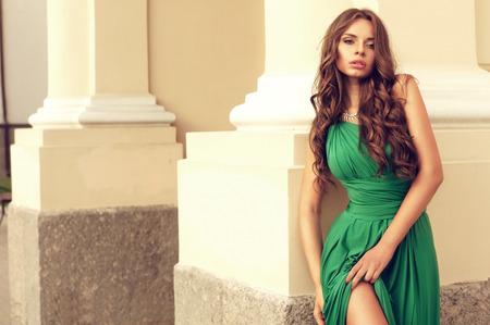 сексуальная дама в зеленом платье стоит возле желтой стены на улице Фото со стока
