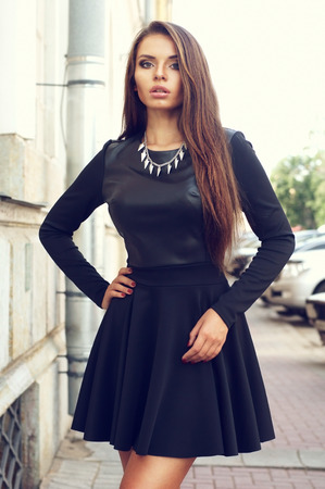 beautiful stylish sexy girl in black dress posing at the street