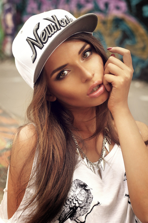 Joven mujer sexy retrato al aire libre en verano en la ciudad. Botín de moda vestido con la camiseta del vintage. Estilo Pasión. Foto de archivo