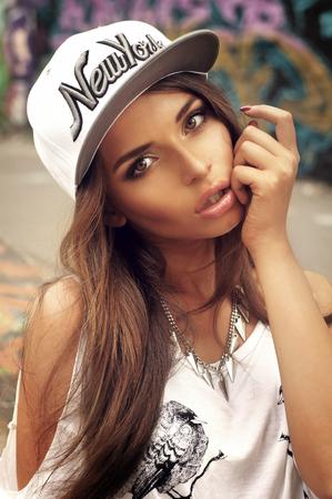 swag: Joven mujer sexy retrato al aire libre en verano en la ciudad. Bot�n de moda vestido con la camiseta del vintage. Estilo Pasi�n. Foto de archivo