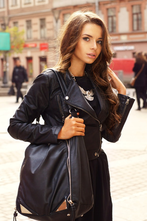 portrait of young stylish girl in black dress and black leather jacket holding big black bag and standing at the street        Foto de archivo