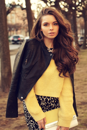 young beautiful woman wearing dress, yellow pullover and leather jacket posing outdoors. stylish fashion portrait        Foto de archivo