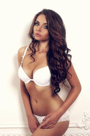 joven y bella chica sexy posando contra la pared blanca