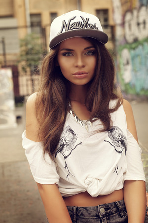 Stylish pretty hipster swagger girl postrat. Outdoor fashion style portrait of young beautiful woman 스톡 콘텐츠