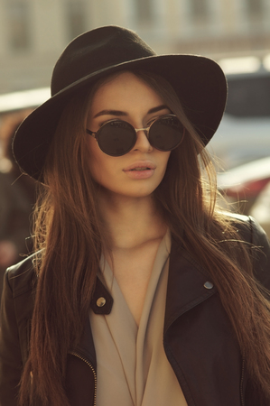 fashion style portrait of young trendy girl in fashionable hat and sunglasses Stockfoto