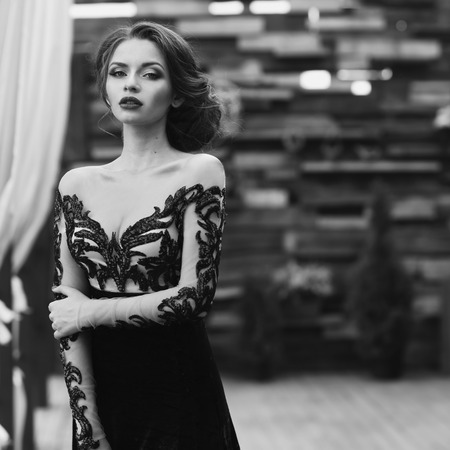 Young stunning beautiful pretty woman in black lace luxury evening dress posing at terracce. Fashion vogue style portrait in black and white colors