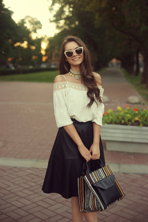 Outdoor portrait of young beautiful stylish smiling woman wearing white blouse, black skirt and sunglasses, holding handbag. Pretty lady looking at you or in camera