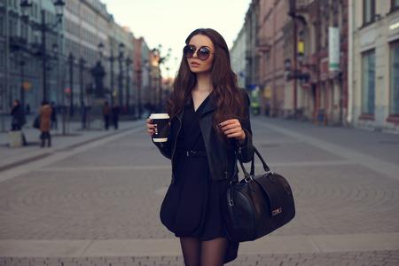 Молодая красивая красивая девушка идет по улице с сумкой и чашкой кофе.