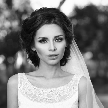 te negro: Closeup portrait of young beautiful bride in white dress and veil looking at you. Black and white photo