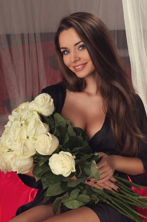 mujer con rosas: Retrato de joven muy hermosa que sostiene gran ramo de rosas blancas y sonriendo