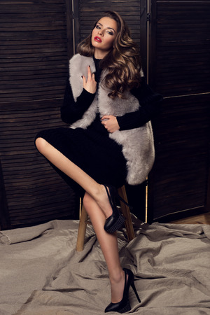 Fashion portrait of young lady in black dress and fur coat sitting on a stool. Pretty girl with dark long curly hair.