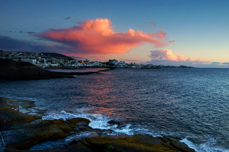 view on a calm bay and stony sea coast at pink sunset