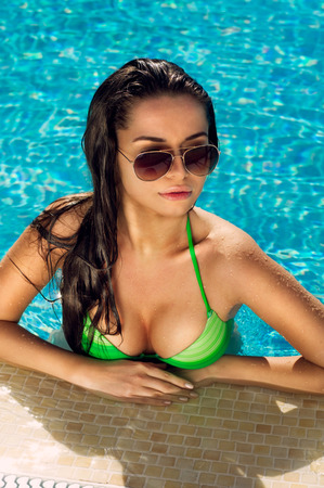 Sexy girl in green bikini in swimming pool. Portrait of young pretty woman in blue water at summer resort.