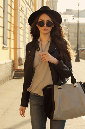 fashion style portrait of young trendy girl walking along the street Stockfoto