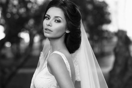 te negro: Retrato de detalle de la joven y bella novia en vestido blanco y un velo que le mira. foto en blanco y negro Foto de archivo