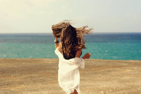 Woman enjoying freedom at ocean coastline on a windy day. View on blue sea Stock Photo