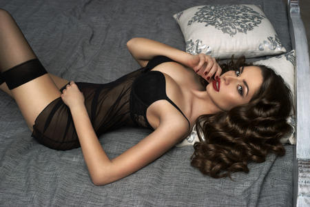 Fashion glamour portrait of young sexy brunette female model lying on bed with long dark wavy hair and red lips in black lingerie and stockings looking at you Stock Photo