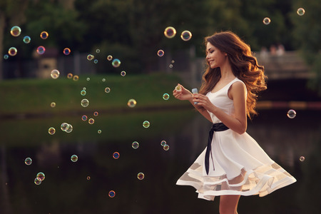 Outdoor summer portrait of young beautiful happy woman making soap bubbles in park or at nature in white dress