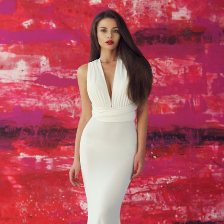 Young beautiful stunning woman posing in long elegant white evening dress and red shoes against stylish red background Stock Photo