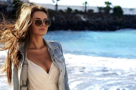 jonge sensuele vrouw met streaming haar wandelen op het strand