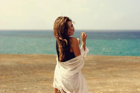 windy: Woman enjoying freedom at ocean coastline on a windy day.