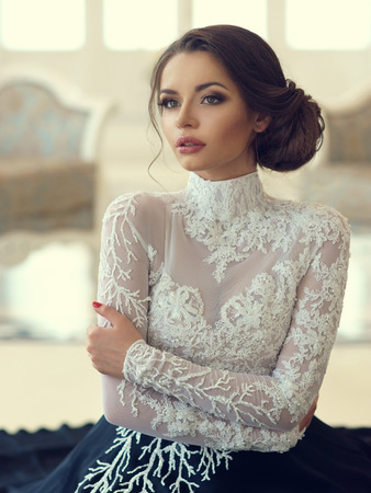 Closeup portrait of young beautiful girl in evening dress and with hairdress sitting on floor in white luxury interiors