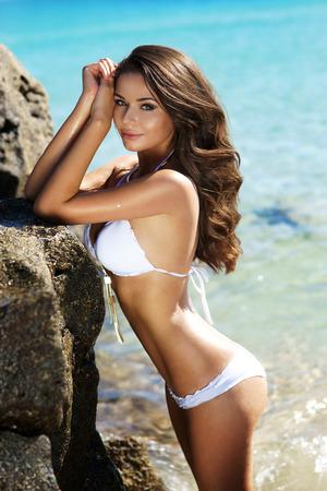 Young beautiful female model standing in blue water near huge rocks in bikini posing on a hot summer sunny day