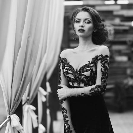 vogue style: Young stunning beautiful pretty woman in black lace luxury evening dress posing at terracce. Fashion vogue style portrait in black and white colors